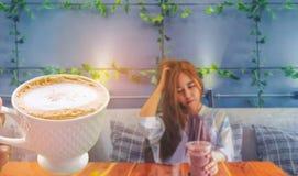 Die abstrakte Weichzeichnung junger Dame, Jugendlichegetränk der kühle Kaffee im Plastikglas im Raum mit dem Strahlnlicht, SH Lizenzfreie Stockfotos
