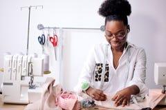 Die afrikanische Näherin, die mit Gewebe arbeitet, ergreift Maßnahmen stockfotos