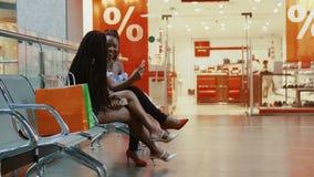 Die afrikanischen Frauen sitzen auf der Bank im Mall stock footage
