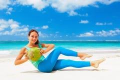 Die aktive Frau, die Sport tut, trainiert mit Kokosnüssen auf Seestrand Lizenzfreie Stockfotos