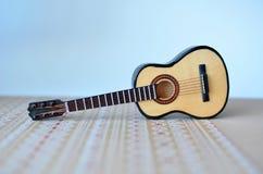 Die Akustikgitarre auf einem Papierhintergrund Stockfotografie