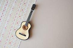 Die Akustikgitarre auf einem Papierverzierungshintergrund Stockfotos