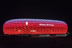 Die Allianz-Arena, das Fußballstadion von FC Bayern, belichtet im Rot mit Weiß auf die Oberseite nachts Lizenzfreie Stockfotos