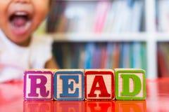 Die Alphabetblöcke, die das Wort buchstabieren, lasen vor einem Bücherregal und einem aufgeregten Kind im Hintergrund stockbilder