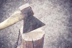 Die alte Axt ist in einem alten Logon der Hintergrund des Bodens fest Lizenzfreies Stockfoto