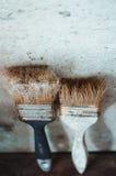 Die alte Bürste nahe der Wand Stockfoto