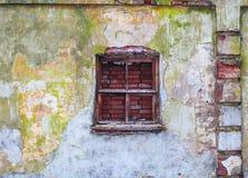 Die alte Backsteinmauer, die bunten schädigenden Gips mit zerbrochener Fensterscheibe bedeckte Lizenzfreies Stockfoto