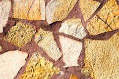 Die alte beige steinige Wand des Hintergrundes Stockbild