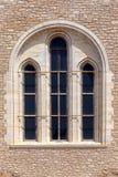 Die alte beige steinige Wand des Hintergrundes mit Marmorfenster Stockfoto