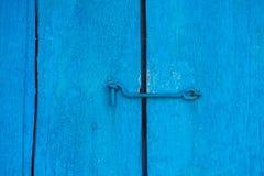 Die alte blaue Tür ist auf dem Haken geschlossen Hintergrund und Beschaffenheit einer alten Holztür Stockfotografie