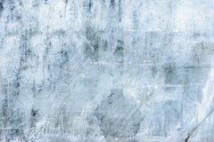 Die alte blaue Wand in den Kratzern und in den Sprüngen Die Beschaffenheit der gebrochenen Farbe und des Gipses Stockfoto