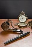 Die alte Borduhr, das Rohr, der Tabak und die Feder. Stockfotografie