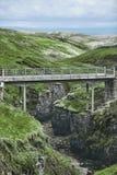 Die alte Brücke über der Schlucht mit einem Strom in den Bergen Stockfoto