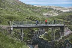 Die alte Brücke über der Schlucht mit einem Strom in den Bergen Stockfotografie