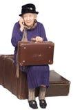 Die alte Dame sitzt auf einem Koffer Lizenzfreie Stockbilder