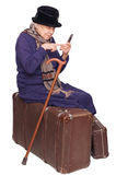 Die alte Dame sitzt auf einem Koffer Lizenzfreie Stockfotografie