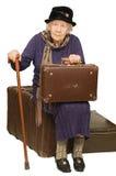 Die alte Dame sitzt auf einem Koffer Stockfotografie