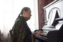 Die alte Dame, die zu Hause klassische Musik auf dem Raritätsklavier spielt Lizenzfreie Stockfotos