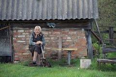 Die alte Frau auf der Bank in der Landschaft Lizenzfreie Stockfotos