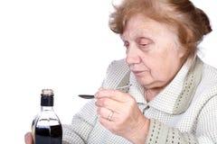 Die alte Frau gießt eine Flüssigkeit Lizenzfreies Stockbild