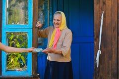 Die alte Frau hält Geld in ihren Händen Eine ältere Frau mit Dollar in ihren Händen stockfotografie