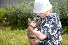 Die alte Frau hält Katze an Stockbild