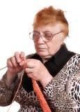 Die alte Frau nimmt an dem Stricken teil Stockfotos