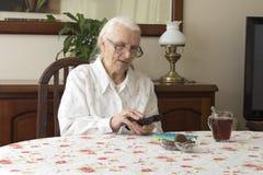 Die alte Frau schaltet die Fernsehfernbedienung ein, die am Tisch sitzt Stockfotos
