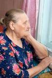 Die alte Frau schaut aus dem Fenster heraus Stockfotografie