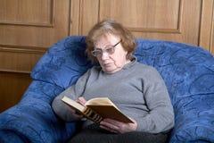 Die alte Frau sitzt in einem Lehnsessel Lizenzfreie Stockbilder