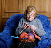 Die alte Frau sitzt in einem Lehnsessel Stockbild