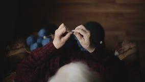 Die alte Frau sitzt zu Hause und strickt Kleider stock video footage