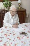 Die alte Frau unterzeichnet die Dokumente, die am Tisch sitzen Stockbilder