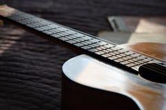 Die alte Gitarre und die Musikbücher beleuchteten durch die Sonne Lizenzfreies Stockbild