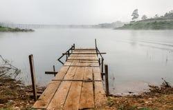 Die alte hölzerne Brücke der Ansicht in Fluss mit Nebel Lizenzfreies Stockfoto