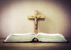 Die alte heilige Bibel über dem Kruzifix auf hölzernem Hintergrund Lizenzfreie Stockfotos