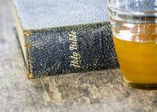 Die alte heilige Bibel mit einer Schale Honig Stockbild