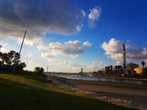 Die alte Industrie, die den grünen Park und das blaue Meer gegenüberstellt lizenzfreies stockfoto
