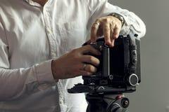 Die alte Kamera auf einem Stativ steht auf einem Hintergrund einer Wand Stockfoto