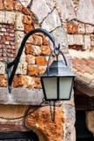 Die alte Laterne, die an einem Backsteinmauerhintergrund hängt Stockfotografie