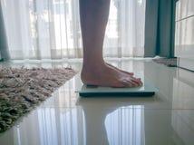 Die alte Mutter ist auf dem Schrecken, zum des Gewichtsverlusts zu messen Stockbild