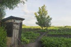 Die alte schiefe Toilette im weiten Dorf Lizenzfreie Stockfotografie