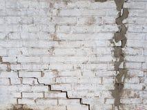 Die alte schmutzige Backsteinmauer ist, mit zwei großen Sprüngen, einer der Sprünge wird bedeckt im grauen Zement, die städtische Stockfotos