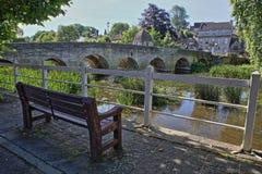 Die alte Stadtbrücke auf dem Fluss Avon mit einer Holzbank im Vordergrund, Bradford auf Avon, Großbritannien Lizenzfreie Stockfotografie