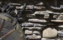 Die alte Steinmetzarbeit mit einem Rad auf Warenkorb Stockbild