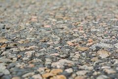 Die alte Straße, die kleinen Steine und der Asphalt nah oben mit einem kleinen dep Lizenzfreie Stockfotografie