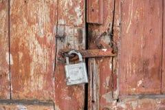 Die alte Tür schloss mit hängenden Klammern eines Vorhängeschlosses zu Stockbild