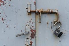 Die alte Tür schloss mit hängenden Klammern eines Vorhängeschlosses zu Lizenzfreie Stockbilder