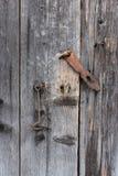 Die alte Tür schloss mit hängenden Klammern eines Vorhängeschlosses zu Stockfotografie