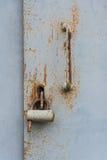 Die alte Tür schloss mit hängenden Klammern eines Vorhängeschlosses zu Satz Hintergründe Stockbilder